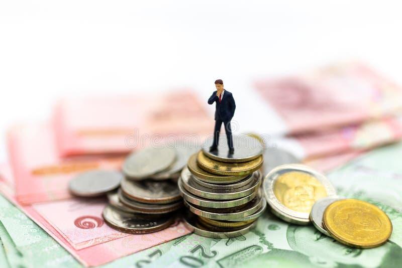 Mini-Personen: Geschäftsmann mit Geld, Der Rhythmus des Marktanteilstreits, die Nutzung des Risikos, Geld, Geschäftskonzept stockfoto
