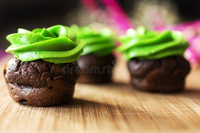 Mini petit gâteau de chocolat avec le givrage de vert de fromage fondu photographie stock libre de droits