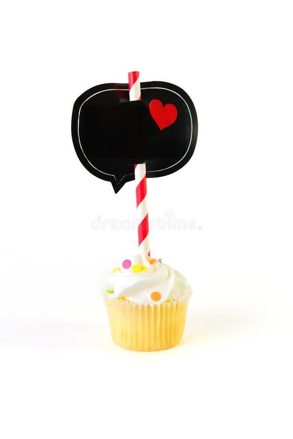 Mini petit gâteau givré avec la bulle et le coeur noirs de la parole sur la bande photos libres de droits