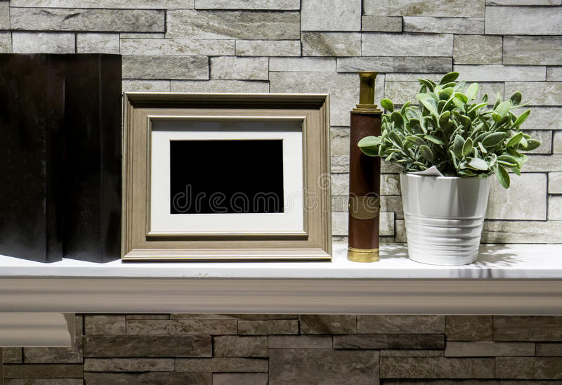 Mini photo frame, vintage candlestick and artificial plant in white clay pot setting on decorative floating wall shelf against st royalty free stock images