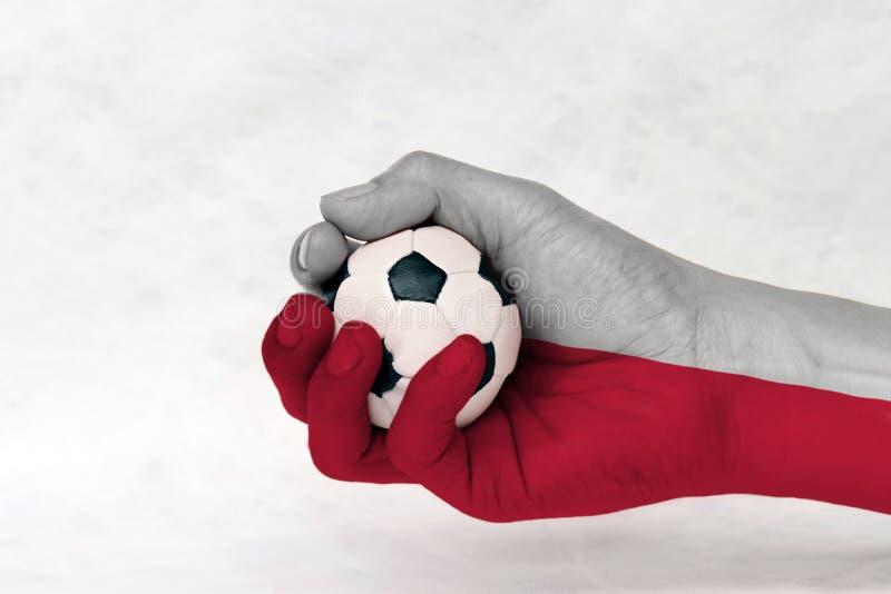 Mini piłka futbol w Polska fladze malował rękę na białym tle Pojęcie sport lub gra w rękojeści lub mniejszościowej sprawie zdjęcia stock
