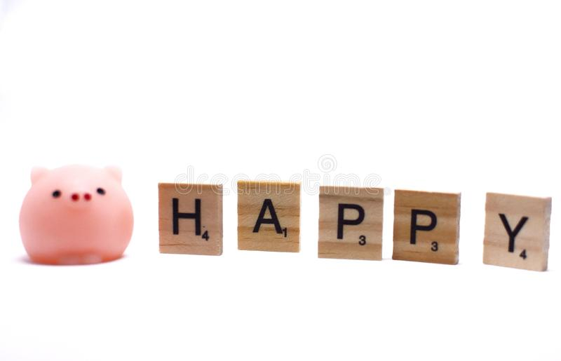 Mini pink pig and the wooden alphabets with word HAPPY, a cute little pig doll and black letters on brown wood, this image isolat royalty free stock photography