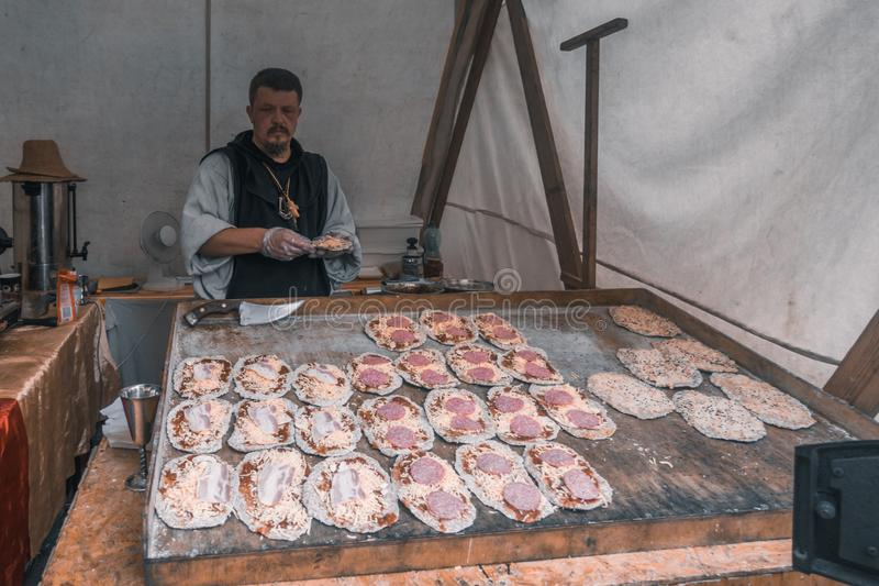 Mini pizza baker in his stall royalty free stock photo