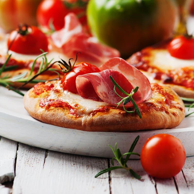 Mini pizza con la mozzarella, il prosciutto di Parma ed il pomodoro immagine stock