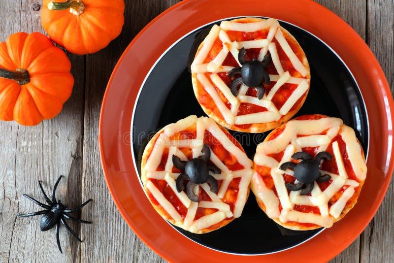 Mini- pizza för allhelgonaaftonspindelrengöringsduk på svart och den orange plattan arkivbilder
