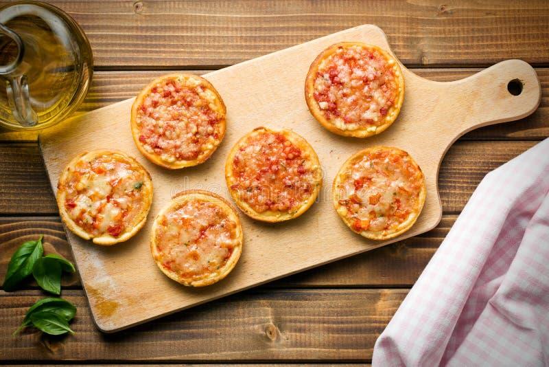 Mini pizza sur la planche à découper image libre de droits