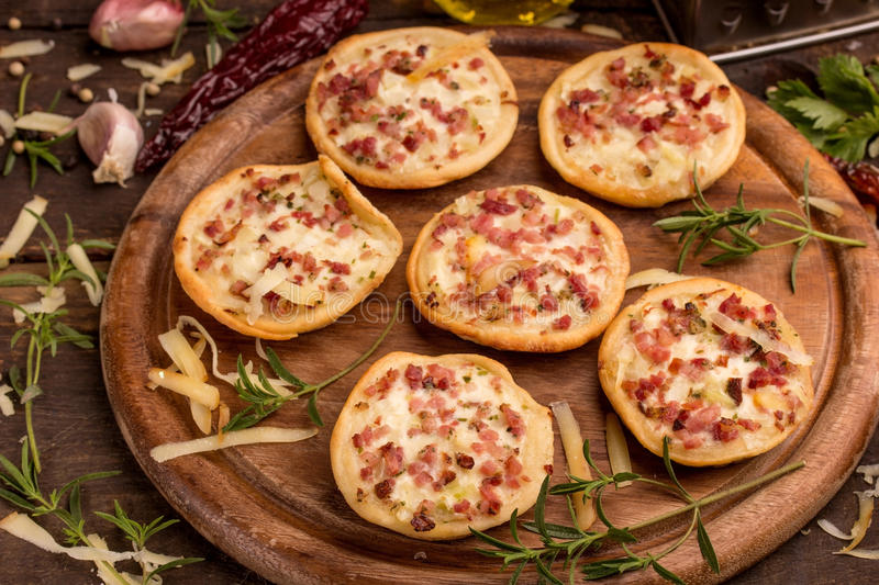 Mini pizzas. And food ingredients on a cutting board royalty free stock photo