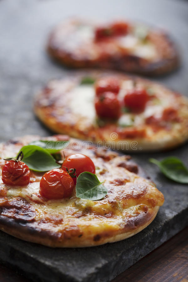 Mini pizzas. Small pizzas with ham, bacon, cheese and tomatoess stock image
