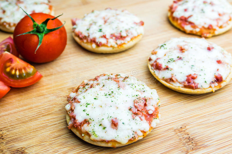 Mini pizzas with tomatoes. Mini pizzas with ham and cheese on wooden plate royalty free stock photography