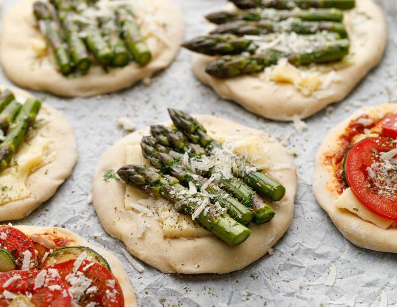 Mini pizze crude con l'aggiunta di asparago, dei pomodori, del formaggio verde e delle erbe per cuocere, primo piano fotografia stock
