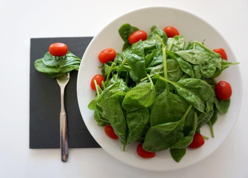Mini pomodori ciliegia e foglie verdi rossi freschi degli spinaci organici del bambino per mangiare immagini stock libere da diritti