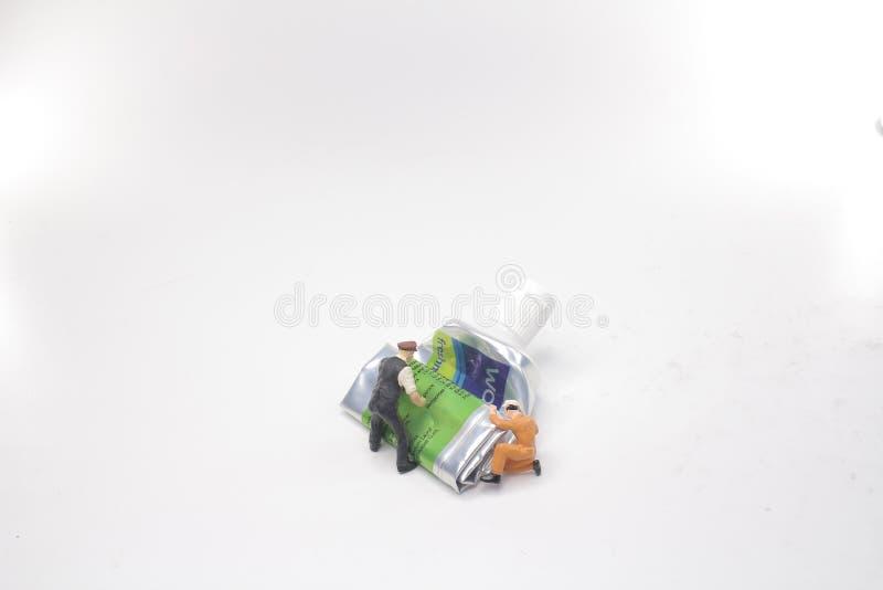 mini postaci pchnięcie tubki pasta do zębów fotografia stock
