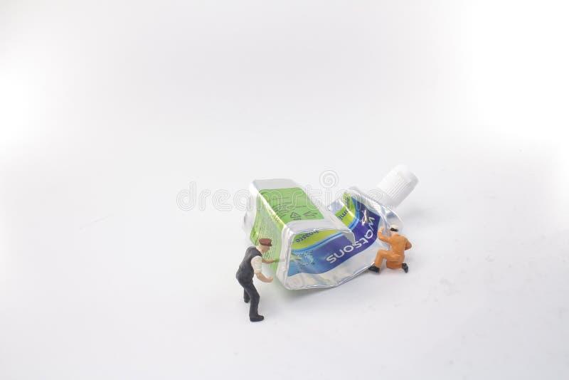 mini postaci pchnięcie tubki pasta do zębów zdjęcia stock