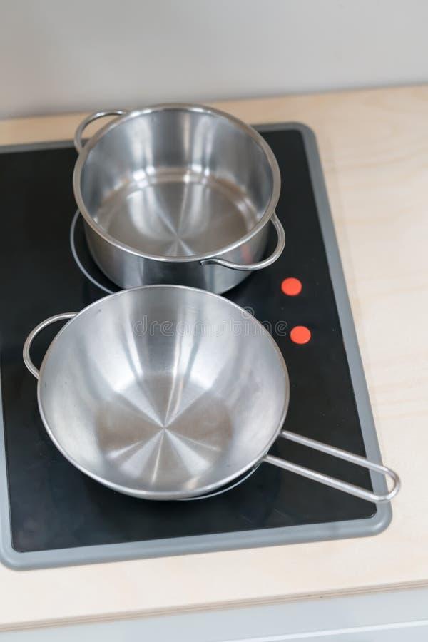 Mini pote y cacerola del acero inoxidable en estufa eléctrica negra sobre el wo fotos de archivo libres de regalías