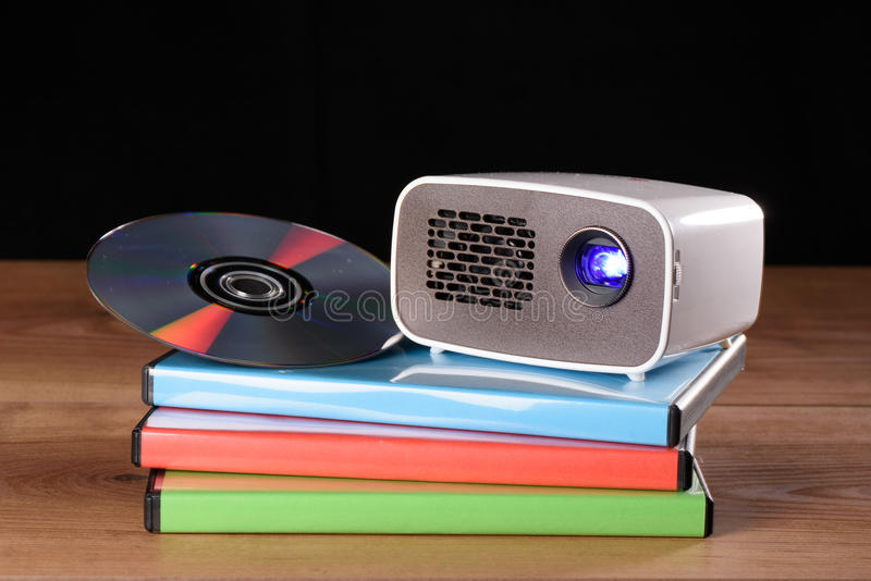 Mini Projector with DVD and DVD cases on wooden table. With black background stock photography