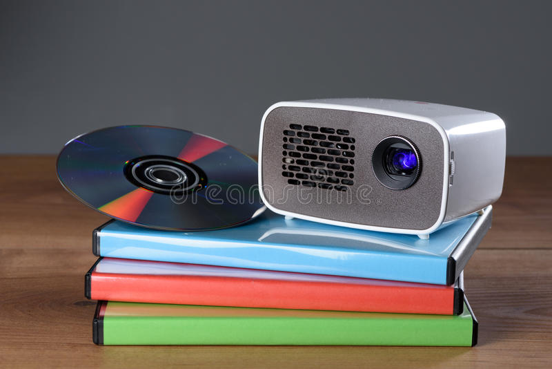 Mini Projector with DVD and DVD cases on wooden table. With grey background royalty free stock photo