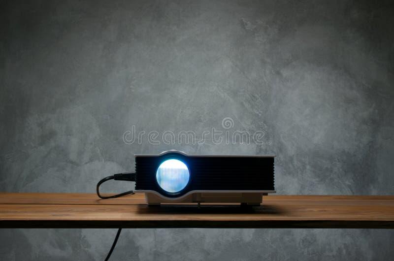 mini proyector llevado en la tabla de madera en un theate del hogar del proyector del sitio imagenes de archivo