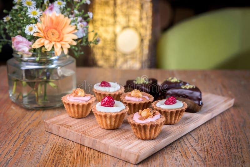 Mini queques caseiros em uma placa de madeira imagens de stock royalty free