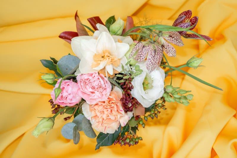 Mini ramo elegante de rosas, de narcisos y de otras flores en un fondo amarillo foto de archivo