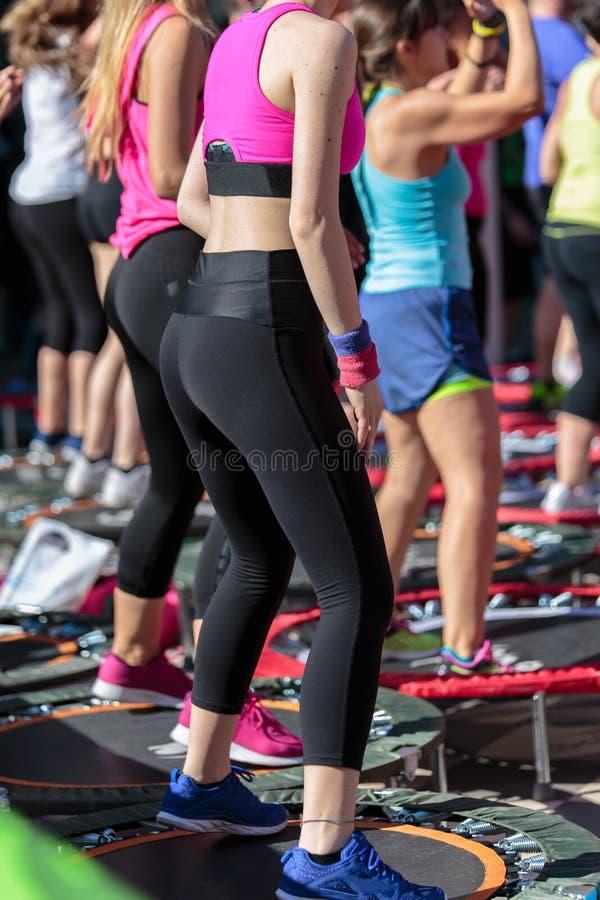 Mini Rebounder Workout: Die Mädchen, die Eignung tun, trainieren Klasse in der im Freien an der Turnhalle stockfotos
