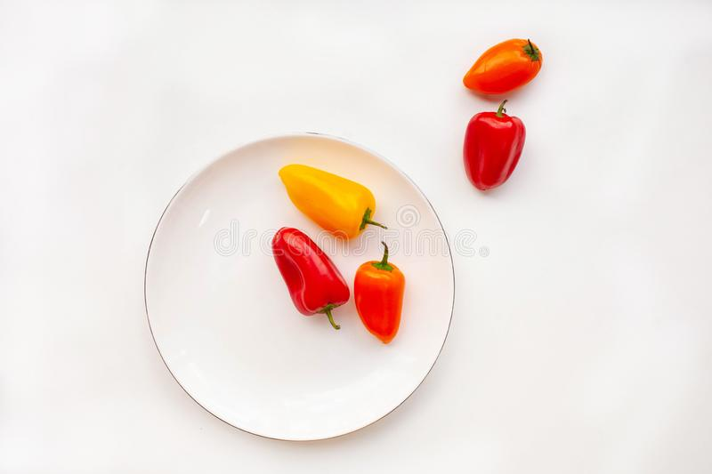 Mini red and orange sweet peppers on a white plate on a white background. horizontal stock photos