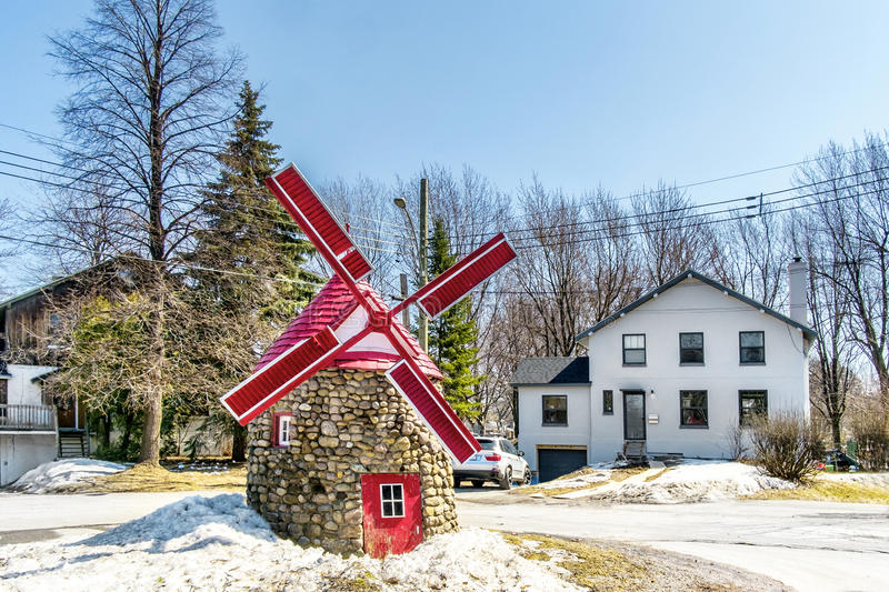 Mini red wind mill. On a dead end street with trees and a blue sky royalty free stock photo
