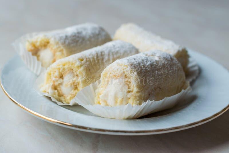 Mini Roll Cake mit Vanille-Creme, Kokosnuss und Puderzucker lizenzfreie stockfotografie