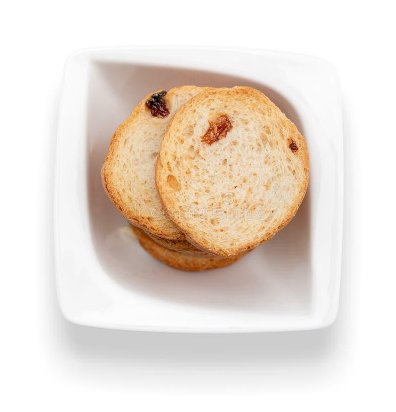 Mini ronde toosts van brood met rozijnen in witte kom Hoogste mening stock foto