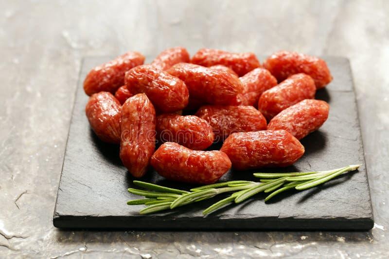 Mini salsichas do salame na tabela de madeira fotos de stock