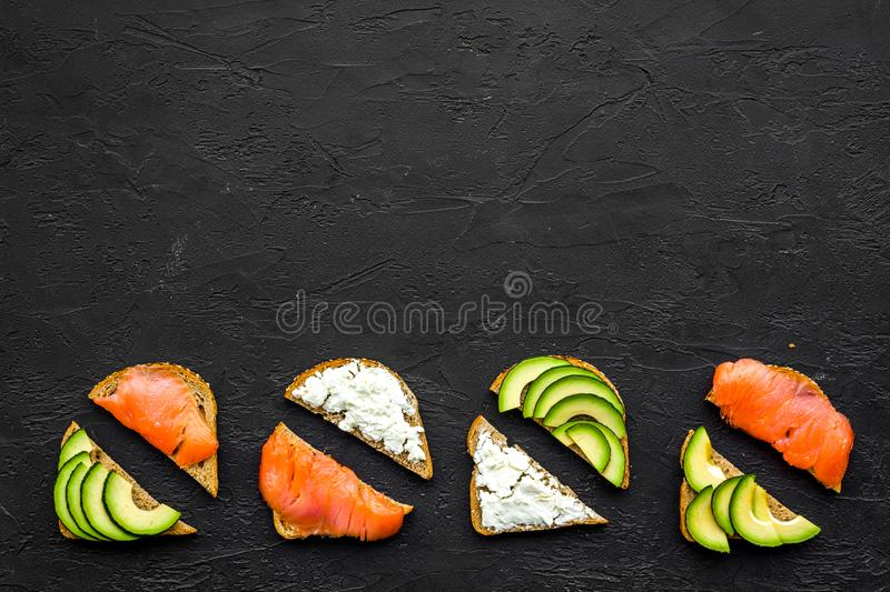 Mini sandwich set with french baguette, cheese, fish and avocado on black background top view mock up stock images
