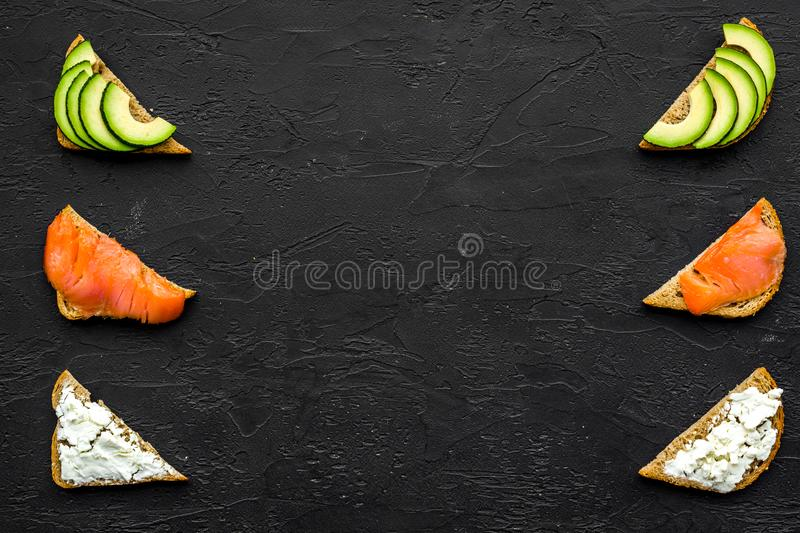 Mini sandwich set with french baguette, cheese, fish and avocado on black background top view mock up royalty free stock images