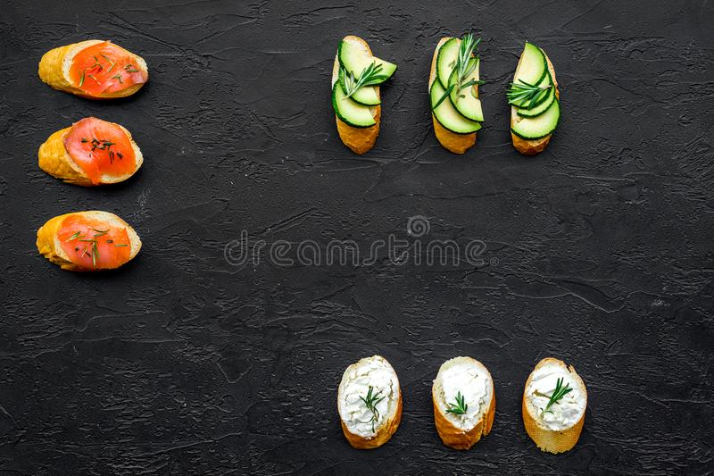 Mini sandwich set with french baguette, cheese, fish and avocado on black background top view mock up stock image