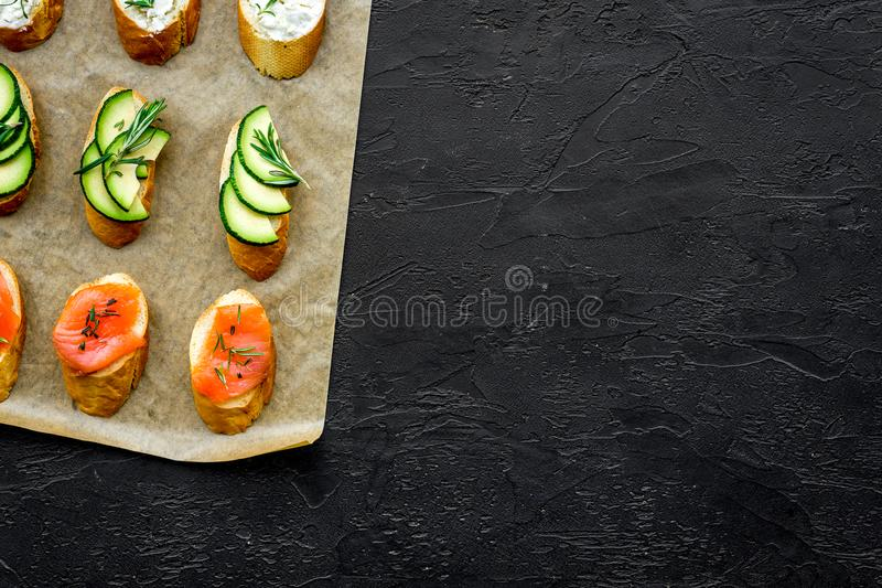 Mini sandwich set with french baguette, cheese, fish and avocado on black background top view mock up royalty free stock image