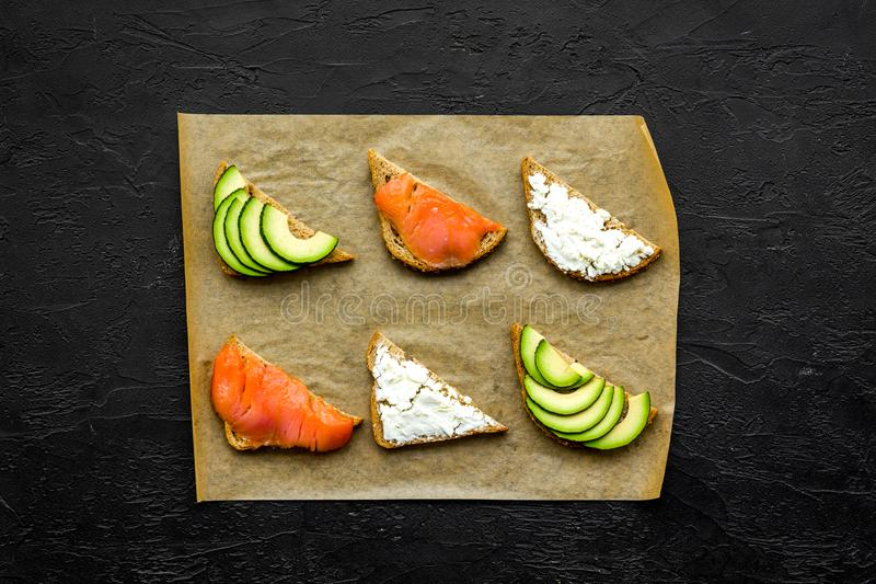 Mini sandwich set with french baguette, cheese, fish and avocado on black background top view mock up stock photography