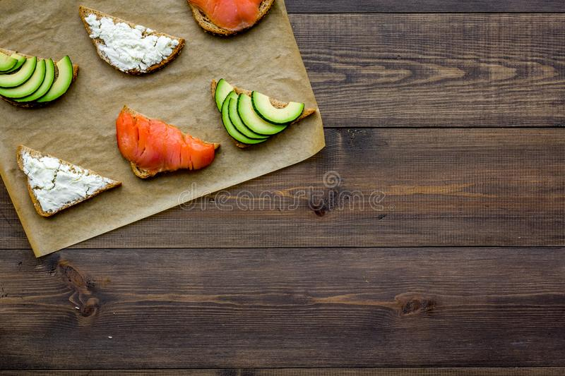 Mini sandwich set with french baguette, cheese, fish and avocado on wooden background top view mock up stock photos