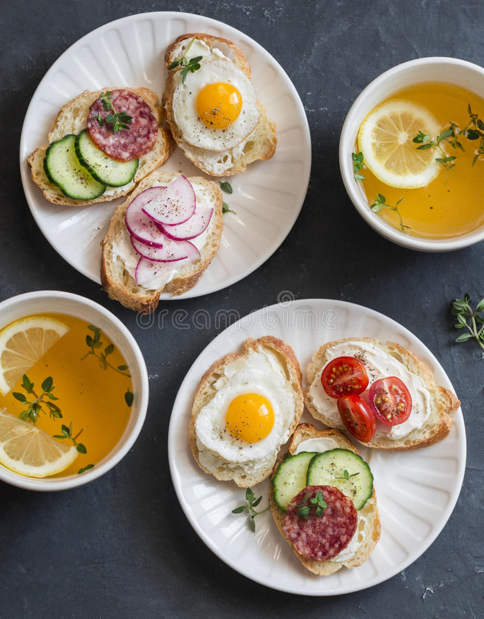 Mini sandwiches with cream cheese, vegetables, quail eggs, salami and green tea with lemon and thyme. Sandwiches with cheese, cucu royalty free stock photo