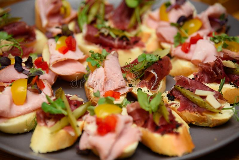 Mini sandwiches with ham and vegetables on the plate. royalty free stock images