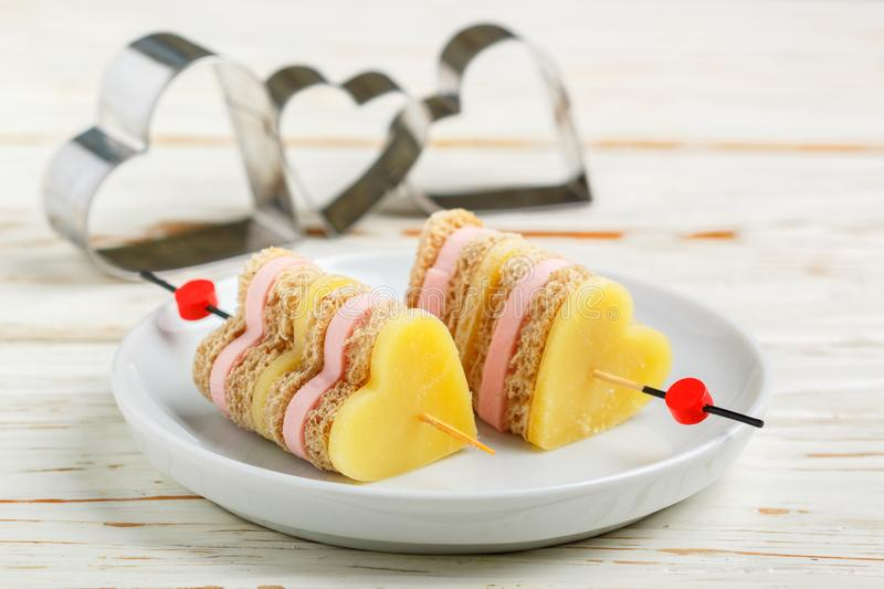Mini sandwiches parmesan cheese ham bread on skewers in the form of hearts. Valentine`s day. Breakfast for loved ones. Selective focus and copy space stock image