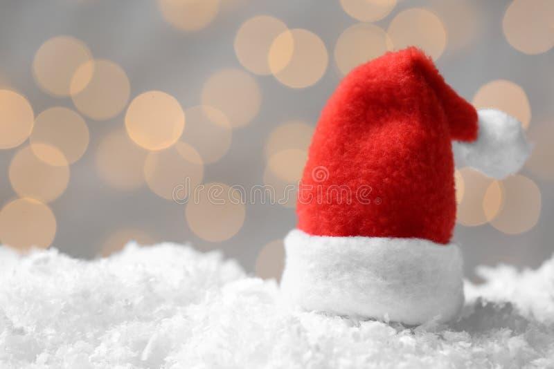 Mini Santa-Hut auf künstlichem Schnee gegen unscharfe Weihnachtslichter lizenzfreies stockfoto