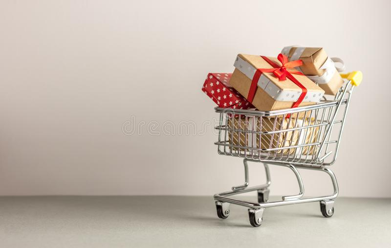 Mini shopping cart with boxes with presents. Mini shopping cart full with boxes of presents stock photography