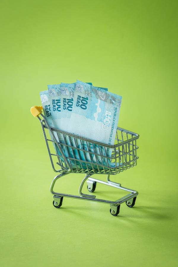 Miniature shopping trolley with Brazilian money. The concept of shopping and the power of the economy. stock photo
