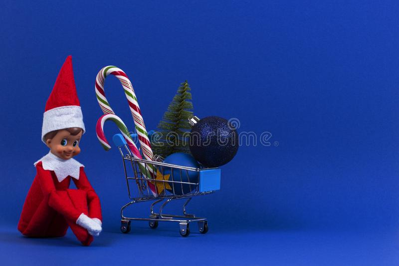 Mini shopping cart with candy canes, little Christmas tree, Xmas decoration bauble balls and toy Santa elf on navy blue. Mini shopping cart with candy canes stock photography