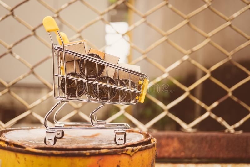 Mini shopping cart contain paper box and coins using as e-commerce, online shopping and business marketing concept. Background, banking, basket, building, buy royalty free stock photography