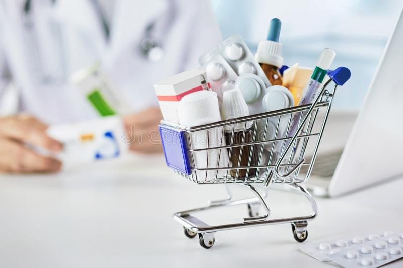 Mini shopping cart with drugs in pharmacy. Close up view of mini shopping cart with drugs in pharmacy royalty free stock images