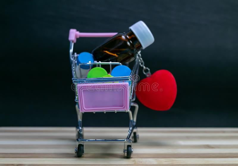 Mini Shopping cart filled with homeopathic medicine bottles with heart on wood and dark background. Online medical concept stock images