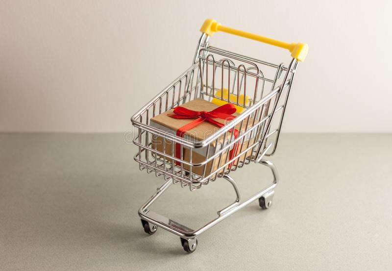 Mini shopping cart with boxes with presents. Mini shopping cart full with boxes of presents stock images