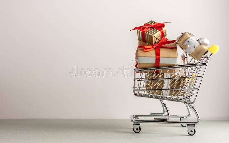 Mini shopping cart with boxes with presents. Mini shopping cart full with boxes of presents royalty free stock photos