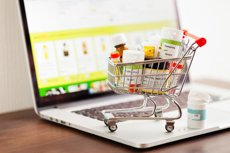 Mini shopping cart full of different homeopathic remedies on laptop background. royalty free stock image