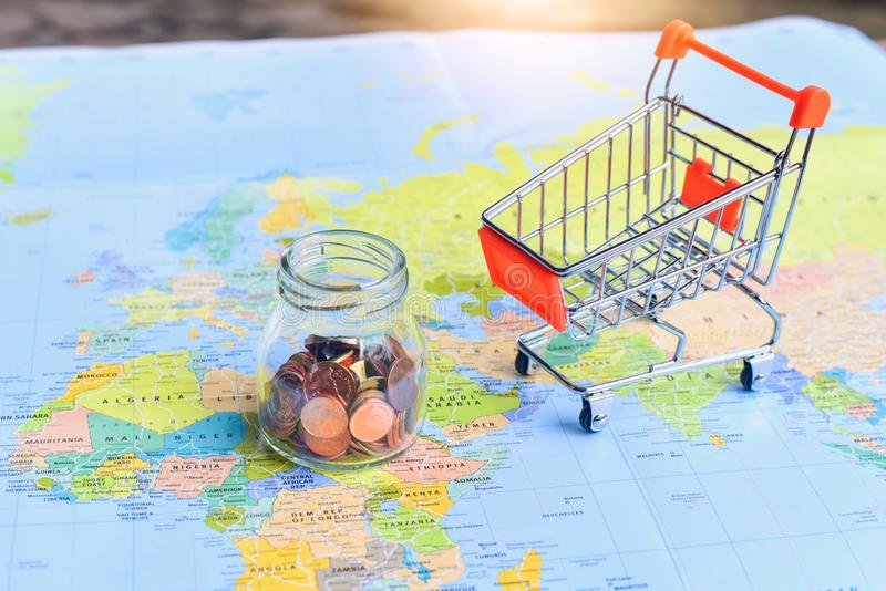 Mini shopping cart and glass jar filled with bronze coins on world download mini shopping cart and glass jar filled with bronze coins on world map stock photo gumiabroncs Gallery