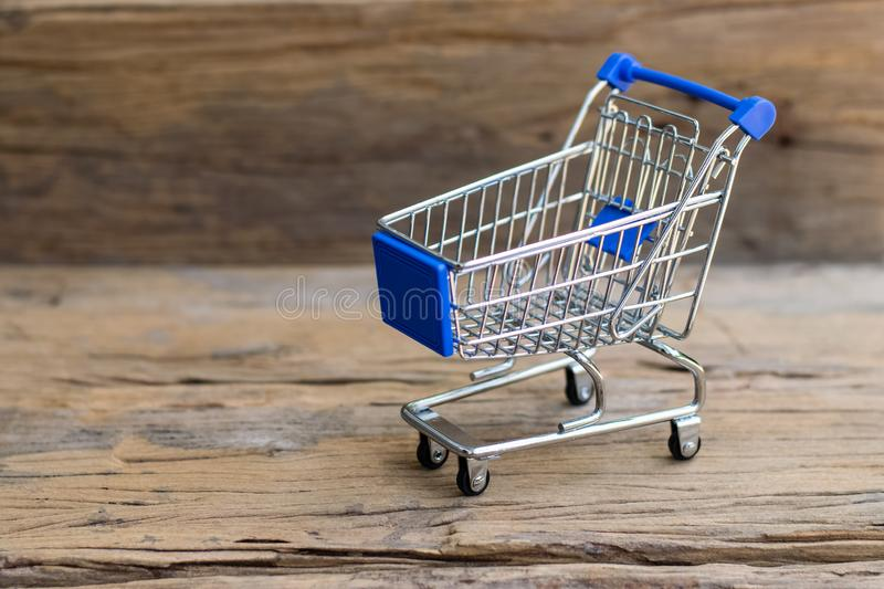 Mini Shopping Cart. Shopping cart on an old wood background. Sale concept stock image